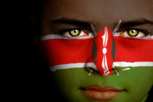 Portrait of a boy with the flag of Kenya painted on his face.